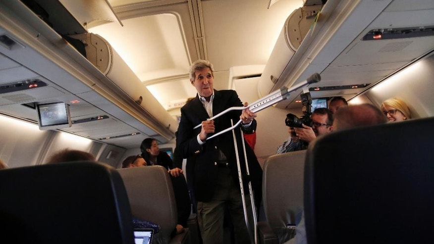 Secretary of State John Kerry plays with his crutches as he talks to reporters before leaving from Andrews Air Force Base, Md., Friday, June 26, 2015, en route to Vienna, Austria. Kerry flies to Vienna on Friday to join negotiators from six powers and Iran seeking an agreement under which Tehran would curb its nuclear program in exchange for relief from economic sanctions that have crippled its economy.   (Carlos Barria/Pool Photo via AP)