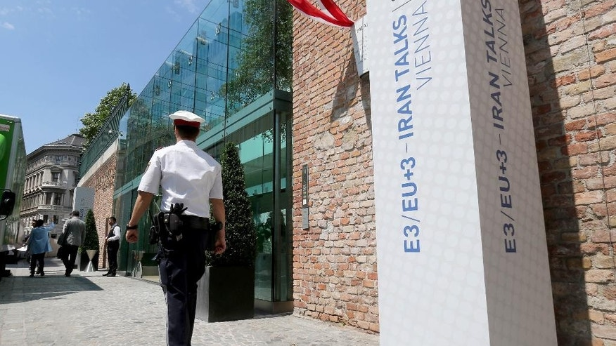 A Police guard walks past Palais Coburg where closed-door nuclear talks with Iran take place  in Vienna, Austria, Friday June 26, 2015. (AP Photo/Ronald Zak)