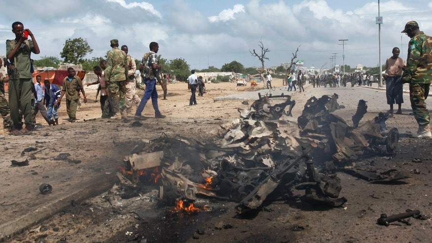 June 24, 2015 - Somali soldiers stand near the wreckage at the scene of a suicide car bomb attack which targeted a convoy of foreign officials, in Mogadishu, Somalia.  Islamic militants from the al Qaeda-linked al-Shabab group attacked a remote African Union base in Somalia Friday, killing 30 in a wave of violence.