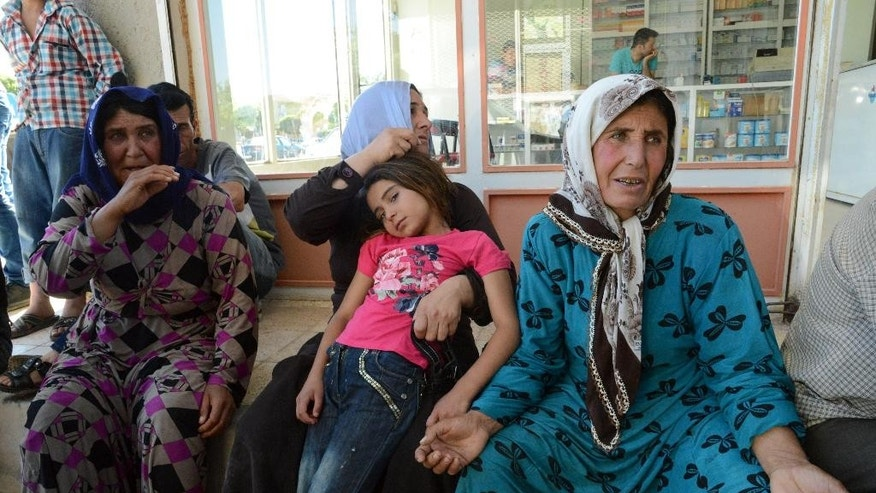 Family members of a wounded person from the Syrian town of Ayn al-Arab or Kobani wait outside a hospital in the border town of Suruc, Turkey, Thursday, June 25, 2015. Islamic State militants launched two major attacks in northern Syria on Thursday, storming government-held areas in the mostly Kurdish city of Hassakeh and pushing into Kobani — the Syrian Kurdish border town they were expelled from early this year — where they set off three cars bombs, killing and wounding dozens, activists and officials said.(AP Photo)