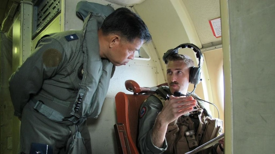 In this photo taken Thursday, June 25, 2015, Western Command deputy commander Brigadier General Guillermo Molina Jr. talks to U.S. Navy officer Patrick Ronan on board a P3 Orion plane during  the joint US-Philippines naval exercise dubbed CARAT (Cooperation Afloat Readiness and Training) 2015 over the Sulu Sea off Palawan Province in western Philippines. The weeklong combat exercises have helped the U.S. and Philippine navies prepare to jointly deal with natural disasters and a range of security challenges. (AP Photo/Jim Gomez)