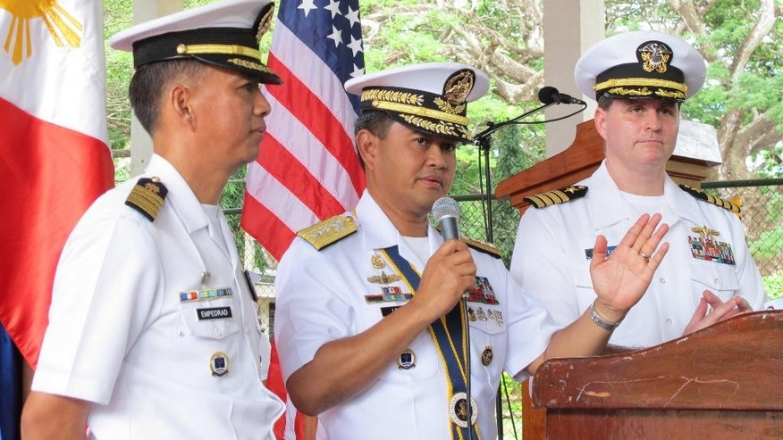 Philippine Navy Vice Admiral Alexander Lopez, center, Commander, Western Command, answers questions from the media at the conclusion of the joint US-Philippines naval exercise dubbed CARAT (Cooperation Afloat Readiness and Training) 2015 at the Naval Forces West headquarters in Puerto Princesa City, Palawan province in western Philippines Friday, June 26, 2015. The weeklong combat exercises have helped the U.S. and Philippine navies prepare to jointly deal with natural disasters and a range of security challenges. At left is Capt. Robert Empedrad, Exercise Director of CARAT 2015, and at right is U.S. Navy Captain Fred Kacher, Commander, Destroyer Squadron 7. (AP Photo/Jim Gomez)