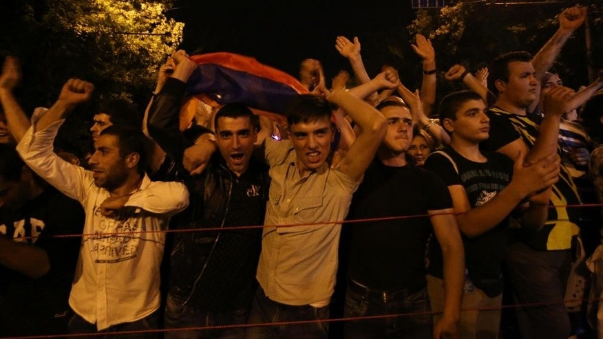 Armenian protesters sing folk songs while waving a national flag during a protest rally against a hike in electricity prices in Yerevan, Armenia, Thursday, June 25, 2015. Armenia's premier has rejected demonstrators' demand to annul a hike in electricity prices, a stance that signals no end in sight for the worst unrest the ex-Soviet nation has seen in years. (Hrant Khachatryan/PAN Photo via AP)