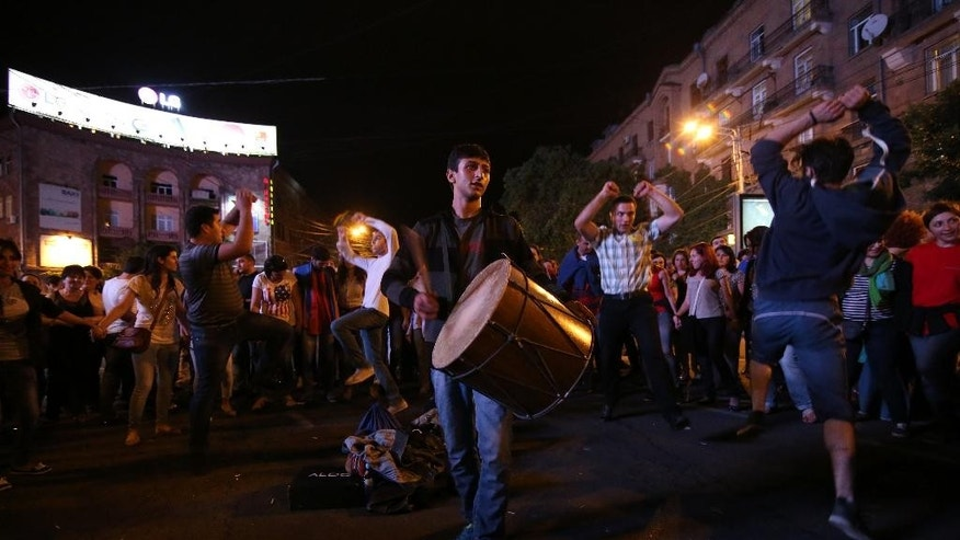 Armenian protesters dance during a protest rally against a hike in electricity prices in Yerevan, Armenia, Thursday, June 25, 2015. Armenia's premier has rejected demonstrators' demand to annul a hike in electricity prices, a stance that signals no end in sight for the worst unrest the ex-Soviet nation has seen in years. (Hrant Khachatryan/PAN Photo via AP)