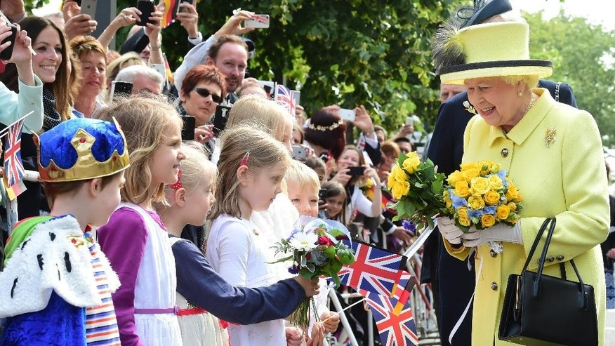 Britain's Queen Elizabeth II, right, is presented with flowers as she walks across the Pariser Platz near Berlin's landmark Brandenburg Gate Friday June 26, 2015, the last day of her state visit to Germany. (John MacDougall/Pool Photo via AP)