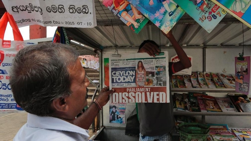 A Sri Lankan man looks at a newspaper at a stall in Colombo, Sri Lanka, Saturday, June 27, 2015. Sri Lanka's President Maithripala Sirisena dissolved Parliament loyal to his predecessor and called fresh elections in August in an attempt to consolidate power and carry out his promise of reforms. (AP Photo/Eranga Jayawardena)