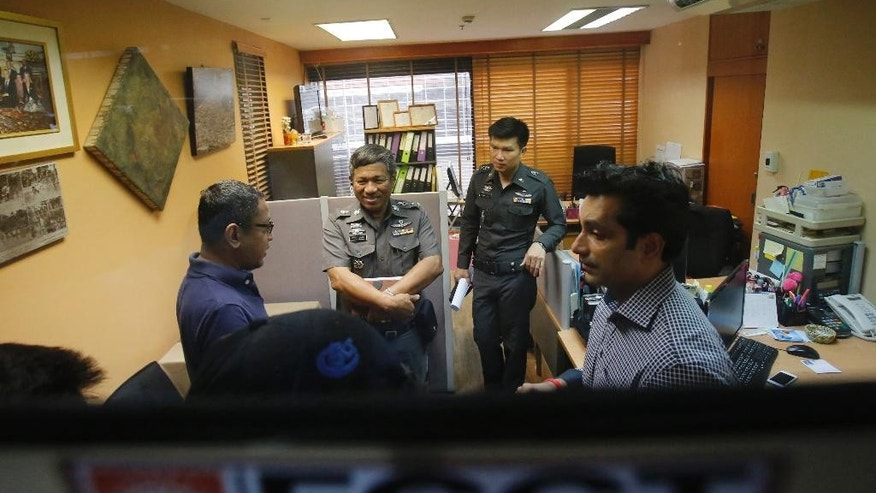 "Sunai Phasuk, left, Human Rights Watch's senior researcher in Asia, and Umesh Pandey, a board member of Foreign Correspondents of Thailand, right, talk to policemen at the Foreign Correspondents Club of Thailand in Bangkok, Thailand Friday, June 26, 2015. Thai authorities on Friday forced the human rights group to cancel the launch of its report on the Vietnamese government's persecution of an ethnic minority, citing it could affect national security and bilateral relations. Thai police said in a statement Friday the scheduled event at the club could ""have an impact on the country's security or could affect the friendship and cooperation between Thailand and Vietnam."" (AP Photo/Sakchai Lalit)"