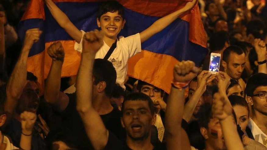 A young protester holds a national flag during a protest rally against a hike in electricity prices in Yerevan, Armenia, late Friday, June 26, 2015. Dancing and singing demonstrators protesting a hike in electricity prices blocked the Armenian capital's main avenue Friday for a fifth straight day, in a tough challenge to the ex-Soviet nation's government. (Hrant Khachatryan/PAN Photo via AP)