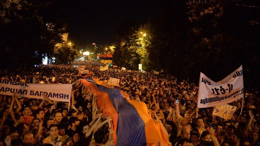 Protesters carry a huge national flag during a protest rally against a hike in electricity prices in Yerevan, Armenia, early Friday, June 26, 2015. Dancing and singing demonstrators protesting a hike in electricity prices blocked the Armenian capital's main avenue Friday for a fifth straight day, in a tough challenge to the ex-Soviet nation's government. (Karo Sahakyan/PAN Photo via AP)