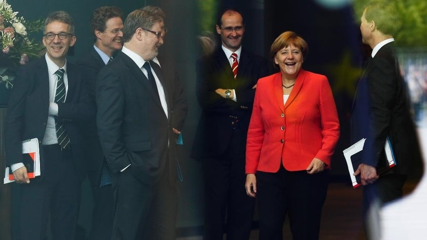 German Chancellor Angela Merkel, 2. from right, laughs with staff on her way to welcomes Britain's Prime Minister David Cameron for bilateral talks at the chancellery in Berlin, Wednesday, June 24, 2015. (AP Photo/Markus Schreiber)