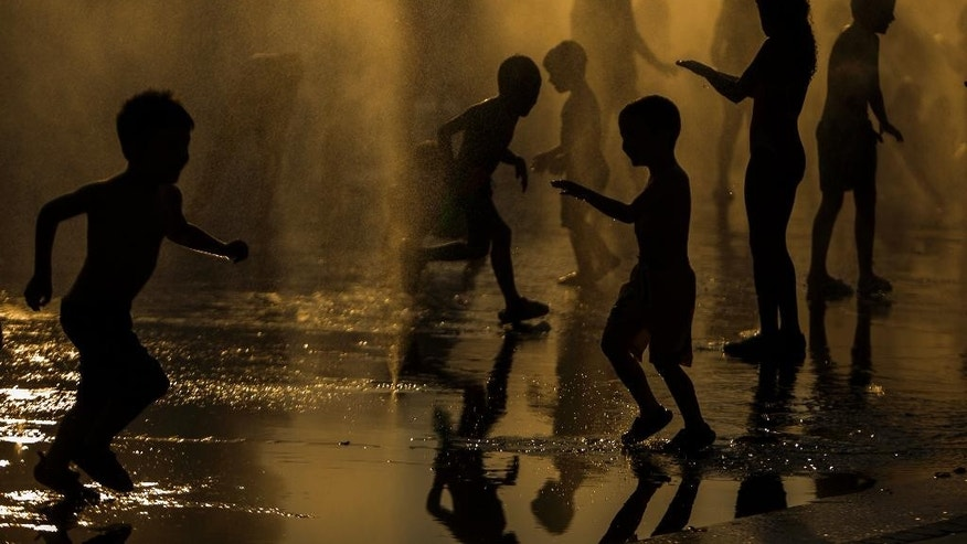 Children cool down in a fountain beside Manzanares river in Madrid,  Spain, Saturday, June 27, 2015. Weather stations across Spain are warning people to take extra precautions as a heat wave engulfs much of the country, increasing the risk of wildfires. The country's meteorological agency says a mass of hot air originating in Africa is moving northwards, bringing with it until at least Monday temperatures reaching 40 C (104 F). (AP Photo/Andres Kudacki)