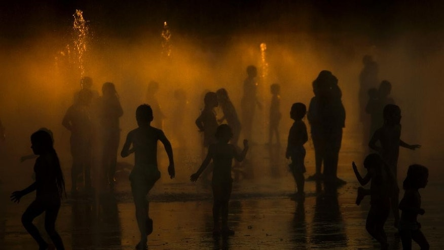 Children play as they cool down in a fountain beside Manzanares river in Madrid,  Spain, Saturday, June 27, 2015. Weather stations across Spain are warning people to take extra precautions as a heat wave engulfs much of the country, increasing the risk of wildfires. The country's meteorological agency says a mass of hot air originating in Africa is moving northwards, bringing with it until at least Monday temperatures reaching 40 C (104 F). (AP Photo/Andres Kudacki)
