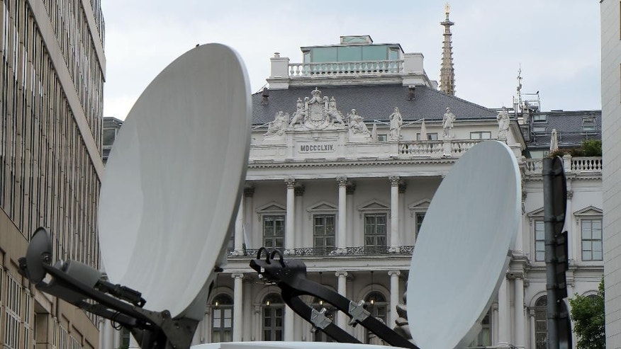 Satellite transmission vans stand in front of Palais Coburg where closed-door nuclear talks with Iran take place in Vienna, Austria, Saturday, June 27, 2015. (AP Photo/Ronald Zak)