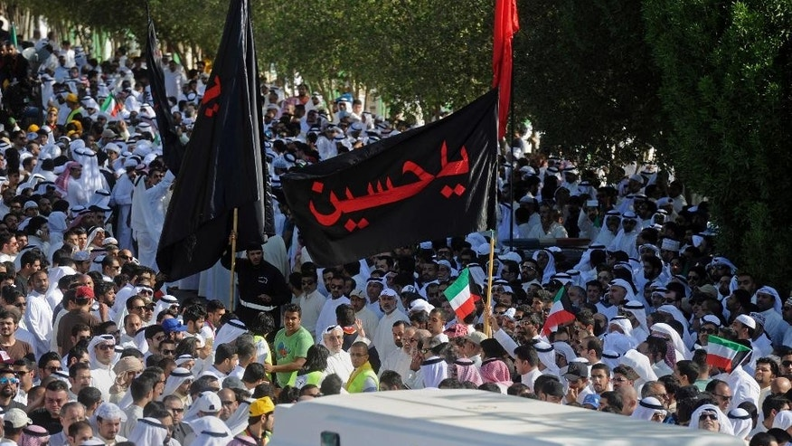 "Thousands of Sunnis and Shiites from across the country take part in a mass funeral procession for 27 people killed in a suicide bombing that targeted the Shiite Imam Sadiq Mosque a day earlier, at the Grand Mosque in Kuwait City, Kuwait, Saturday, June 27, 2015. Police in Kuwait said they are interrogating a number of suspects with possible links to the bombing, which was claimed by an affiliate of the Islamic State group. Arabic writing on flag reads, ""Ya Hussein."" (AP Photo)"