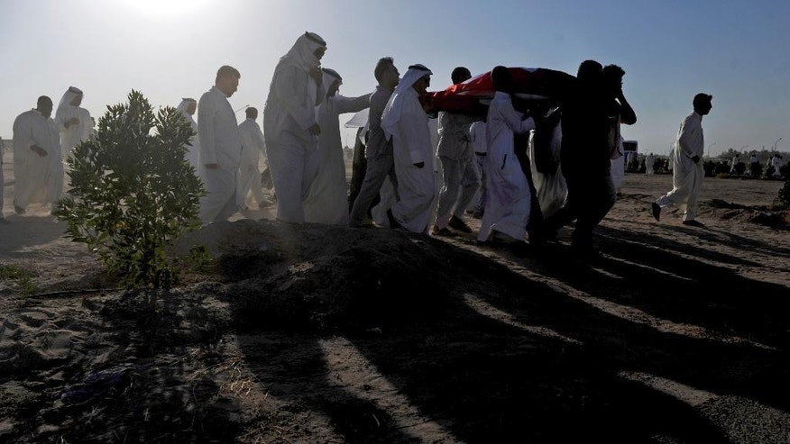 People carry the body of a victim as they take part in a mass funeral procession for 27 people killed in a suicide bombing that targeted a Shiite mosque a day earlier, at the Imam Sadiq Mosque in Kuwait city, Kuwait. Police said they are interrogating a number of suspects with possible links to the bombing, which was claimed by an affiliate of the Islamic State group. (AP Photo)