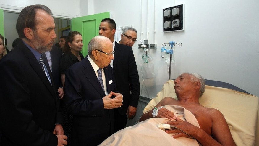 In this photo dated Friday, June 26, 2015, Tunisian President Beji Caid Essebsi, 2nd left, visits a survivor of a terrorist attack in an hospital in the costal town of Sousse, Tunisia. A young man pulled a Kalashnikov from a beach umbrella and sprayed gunfire at European sunbathers at a Tunisian resort, killing at least 39 people — one of three deadly attacks Friday from Europe to North Africa to the Middle East that followed a call to violence by Islamic State extremists. (Slim Abid/Tunisian Presidential Palace via AP)