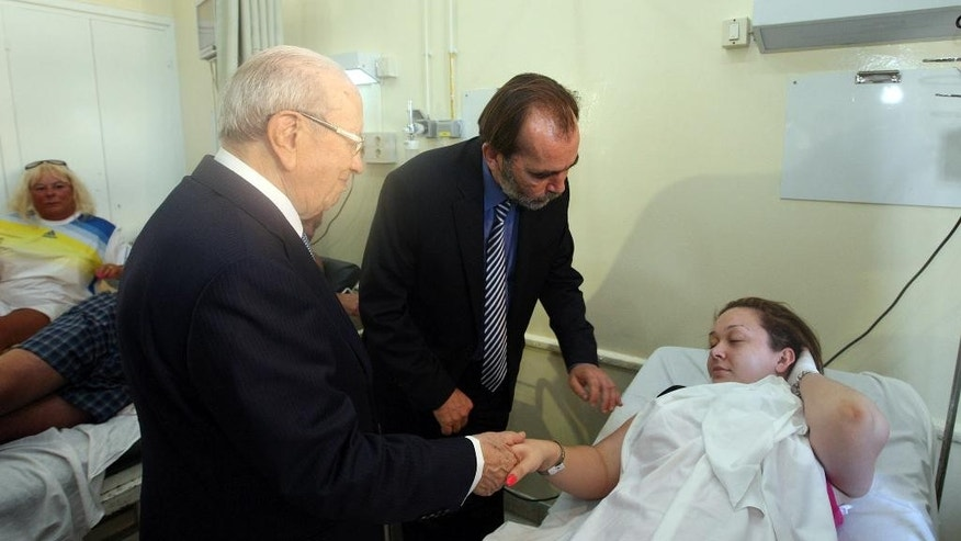 In this photo dated Friday, June 26, 2015, Tunisian President Beji Caid Essebsi, left, visits a survivor of a terrorist attack in an hospital in the costal town of Sousse, Tunisia. A young man pulled a Kalashnikov from a beach umbrella and sprayed gunfire at European sunbathers at a Tunisian resort, killing at least 39 people — one of three deadly attacks Friday from Europe to North Africa to the Middle East that followed a call to violence by Islamic State extremists. (Slim Abid/Tunisian Presidential Palace via AP)