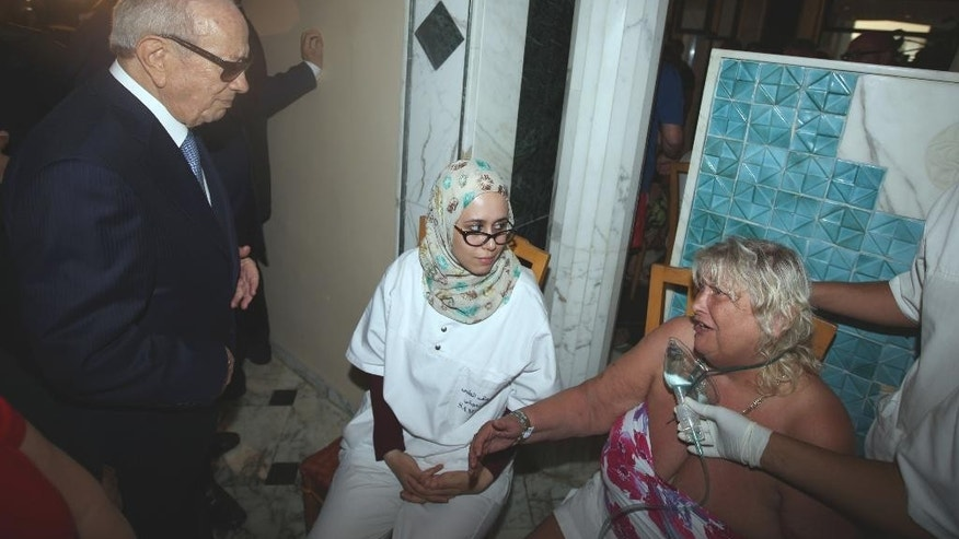 In this photo dated Friday, June 26, 2015, Tunisian President Beji Caid Essebsi, left, visits a survivor of a terrorist attack, right, in an hospital in the costal town of Sousse, Tunisia. A young man pulled a Kalashnikov from a beach umbrella and sprayed gunfire at European sunbathers at a Tunisian resort, killing at least 39 people — one of three deadly attacks Friday from Europe to North Africa to the Middle East that followed a call to violence by Islamic State extremists. (Slim Abid/Tunisian Presidential Palace via AP)