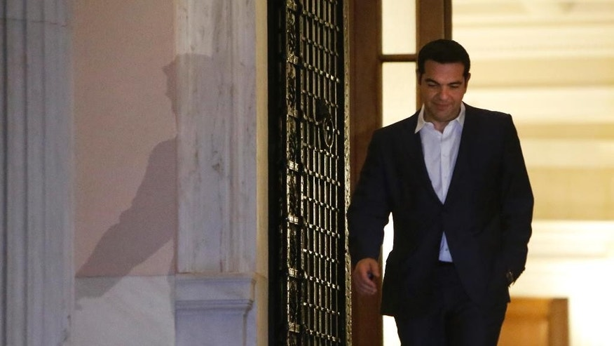 Greek Prime Minister Alexis Tsipras leaves the Maximos Mansion after he announced the referendum in a televised address in central Athens, early Saturday, June 27, 2015. Greece's fraught bailout talks with its creditors took a dramatic turn early Saturday, with the radical left government announcing a referendum in just over a week on the latest proposed deal - and urging voters to reject it. (AP Photo/Petros Karadjias)