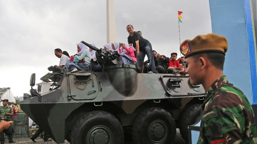 In this Friday, Dec. 12, 2014 photo, Indonesians ride on an Army armored vehicle during an exhibition in Jakarta, Indonesia. Nearly two decades after dictator Suharto forced Indonesia's military out of politics, the army is inching back into civilian roles, risking a setback for democracy in this Southeast Asian nation and perhaps even for the region. (AP Photo/Tatan Syuflana)