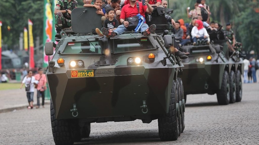 In this Friday, Dec. 12, 2014 photo, Indonesians ride on Army's armored vehicles during an exhibition in Jakarta, Indonesia. Nearly two decades after the fall of dictator Suharto forced Indonesia's military out of politics, the army is inching back into civilian roles, risking a setback for democracy in this Southeast Asian nation. (AP Photo/Tatan Syuflana)