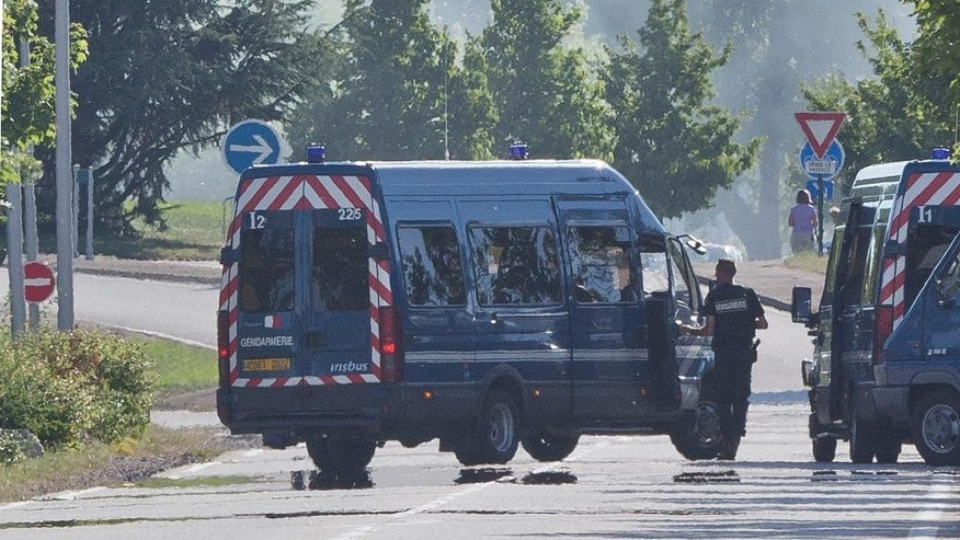 Police officers guard the road leading to a plant in Saint-Quentin-Fallavier, southeast of Lyon, France, Saturday, June 27, 2015, where an attack took place yesterday June 26. A spokeswoman for the Paris prosecutor's office says one of the four suspects detained over an explosion and beheading in southeast France has been released, while the suspected assassin isn't speaking to investigators. (AP Photo/Michel Euler)