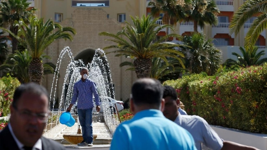 A worker cleans the garden of the Imperial Marhaba hotel where a shooting attack took place Friday in Sousse, Tunisia, Saturday, June 27, 2015. The morning after a lone gunman killed dozens of people at a beach resort in Tunisia, busloads of tourists are heading to the nearby Enfidha-Hammamet airport hoping to return to their home countries. (AP Photo/Darko Vojinovic)