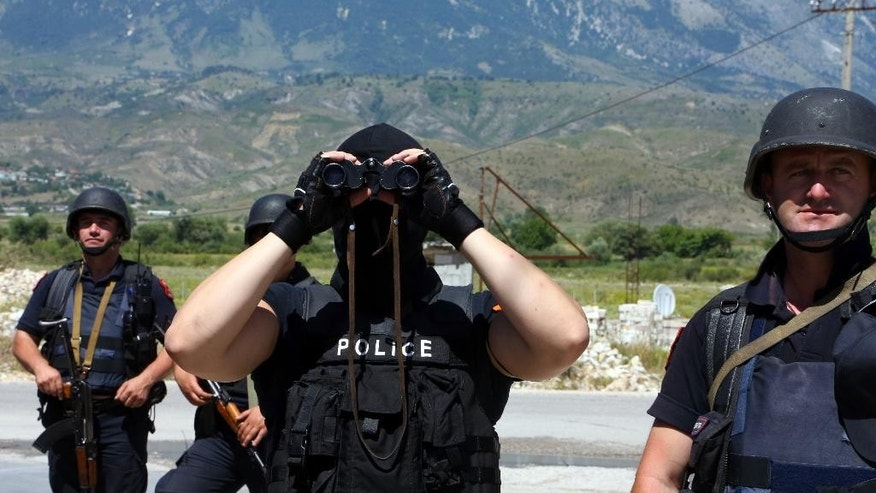 An Albanian police officer uses binoculars during an operation in Lazarat village, about 200 kilometers (125 miles) south of Tirana, Thursday, June 25, 2015. Hundreds of Albanian police officers were checking houses Thursday in a marijuana-growing village in southern Albania a day after gunmen fatally shot a policeman and wounded two others during a shootout. (AP Photo/Hektor Pustina)