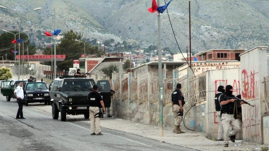 Albanian police officers patrol the scene in Lazarat village, about 200 kilometers (125 miles) south of capital Tirana, Friday, June 26, 2015. Hundreds of police deployed there have already arrested 14 persons and check the village, a major illegal marijuana-growing center, after gunmen fatally shot one policeman and wounded two others a day before. (AP Photo)
