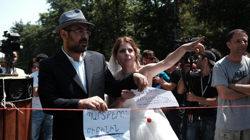"Armenian newly weds adjust leaflets reading, ""Armenian electricity network to Armenia"", to a barricade across a street in downtown Yerevan , Armenia, Sunday, June 28, 2015. The president of Armenia on Saturday suspended hikes in household electricity rates in an effort to end the protests that have blocked the capital's main avenue for six straight days. The demonstrators, however, didn't disperse. (Areg Balayan/ PAN Photo via AP)"