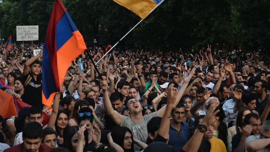 Demonstrators wave national flags during a protest rally against a hike in electricity prices in Yerevan, Armenia, Saturday, June 27, 2015. The president of Armenia on Saturday suspended hikes in household electricity rates in an effort to end the protests that have blocked the capital's main avenue for six straight days. The demonstrators, however, didn't disperse. (Karo Sahakyan/PAN Photo via AP)