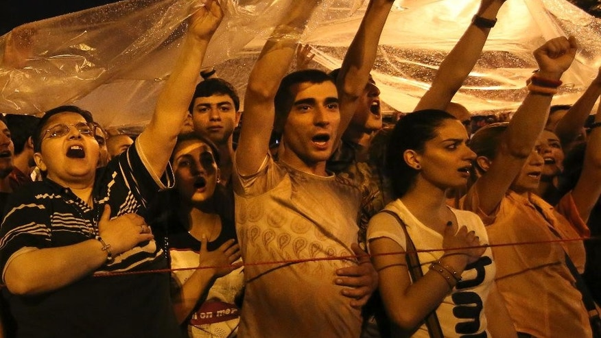 Demonstrators sing patriotic songs during a protest rally against a hike in electricity prices in Yerevan, Armenia, Saturday, June 27, 2015. The president of Armenia on Saturday suspended hikes in household electricity rates in an effort to end the protests that have blocked the capital's main avenue for six straight days. The demonstrators, however, didn't disperse. (Hrant Khachatryan/PAN Photo via AP)