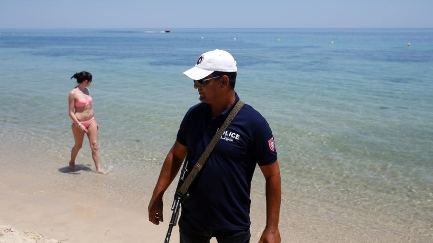 A Tunisian police officer guards the beach area in front of the attacked Imperial Marhaba Hotel in Sousse, Tunisia, Sunday, June 28, 2015. Tunisia's top security official says 1,000 extra police are being deployed at tourist sites and beaches in the North African nation. (AP Photo/Darko Vojinovic)