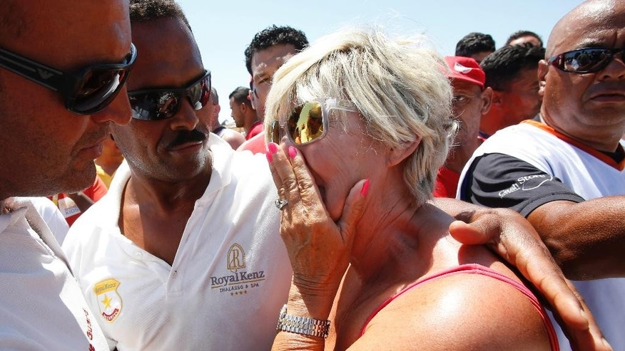 CAPTION CORRECTION, CORRECTS DATE IN CAPTION - A British resident of Sousse, who refused to be identified, reacts during a gathering at the scene of the attack in Sousse, Tunisia, Sunday, June 28, 2015. The Friday attack on tourists at a beach is expected to be a huge blow to Tunisia's tourism sector, which made up nearly 15 percent of the country's gross domestic product in 2014. (AP Photo/Abdeljalil Bounhar)