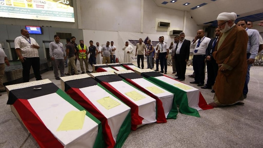 In this Saturday, June 27, 2015 photo, coffins draped with Kuwaiti flags belonging to victims of a suicide bombing that targeted a Shiite mosque in Kuwait on Friday, arrive to Najaf Airport, for the funeral procession at the holy Shiite of Imam Ali, the son-in-law and cousin of the 7th century Prophet Muhammad and the first Imam of the Shiites, in the Shiite holy city of Najaf, Iraq. (AP Photo/Jaber al-Helo)