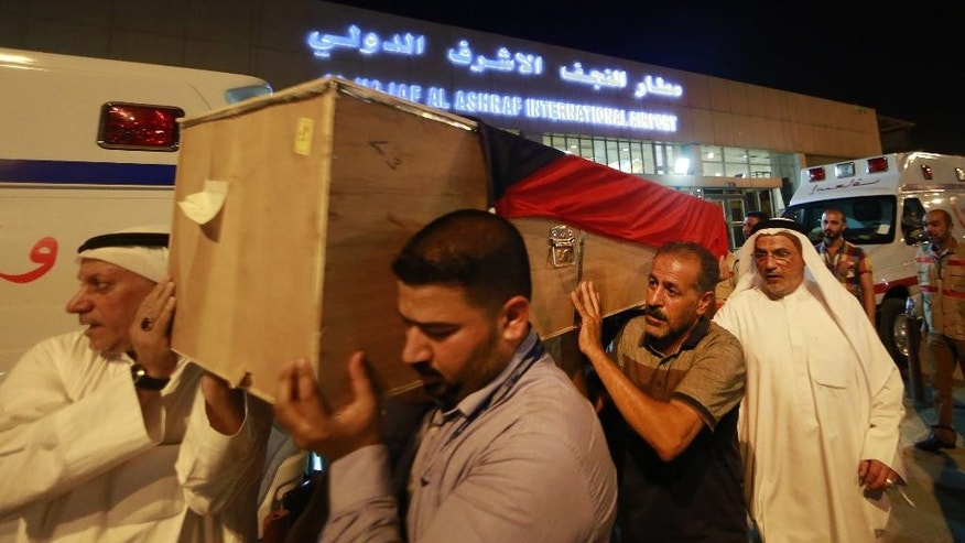 In this Saturday, June 27, 2015 photo, a coffin draped with a Kuwaiti flag belonging to a victim of a suicide bombing that targeted a Shiite mosque in Kuwait on Friday, arrives to Najaf Airport, for the funeral procession, in the Shiite holy city of Najaf, Iraq. Kuwaiti authorities on Sunday identified the suicide bomber behind an attack on a Shiite mosque that killed more than two dozens as a Saudi citizen who flew into the Gulf nation just hours before he blew himself up. (AP Photo/ Jaber al-Helo)