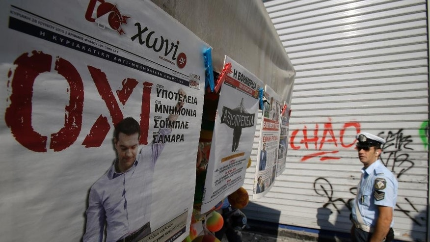 A traffic police officer looks the newspapers' front pages as the paper on the left reads ''NO'' with photo of the Greek Prime minister Alexis Tipras and the next one ''Dignity'' in Athens, Sunday, June 28, 2015. Greece's parliament voted early Sunday in favor of Prime Minister Alexis Tsipras' motion to hold a July 5 referendum on creditor proposals for reforms in exchange for loans, with the country's future in the eurozone looking increasingly shaky. (AP Photo/Thanassis Stavrakis)