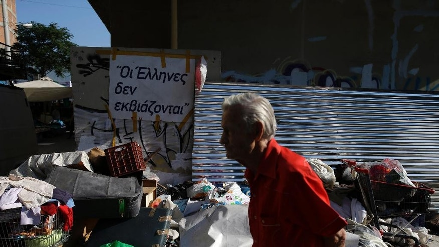 An elderly man passes a sign reads ''Greeks can't be blackmailed'' at a flea market in the port of Piraeus, near Athens, Sunday, June 28, 2015. Greece's parliament voted early Sunday in favor of Prime Minister Alexis Tsipras' motion to hold a July 5 referendum on creditor proposals for reforms in exchange for loans. (AP Photo/Thanassis Stavrakis)