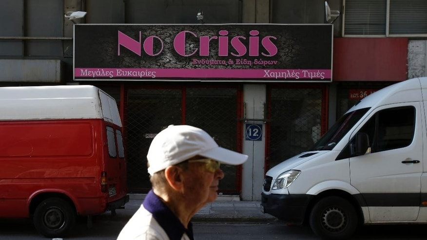 An elderly man passes a shut gift shop as the sign reads ''Great Bargains - Low Prices'' in the port of Piraeus, near Athens, Sunday, June 28, 2015.  Greece's parliament voted early Sunday in favor of Prime Minister Alexis Tsipras' motion to hold a July 5 referendum on creditor proposals for reforms in exchange for loans. (AP Photo/Thanassis Stavrakis)