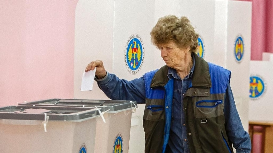 A woman casts her ballot in runoff local elections in Chisinau, Moldova, Sunday, June 28, 2015. Moldovans were voting Sunday in local election runoffs that are being seen as a test of whether the former Soviet republic moves closer to the European Union or Russia. (AP Photo/Dan Morar)