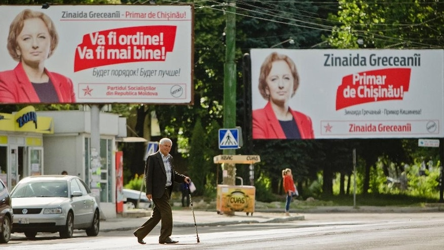 A man crosses the street backdropped by posters of Zinaida Greceanai, the pro-Russian candidate for mayor of the Moldovan capital in Chisinau, Moldova, Sunday, June 28, 2015. Moldovans were voting Sunday in local election runoffs that are being seen as a test of whether the former Soviet republic moves closer to the European Union or Russia. (AP Photo/Dan Morar)