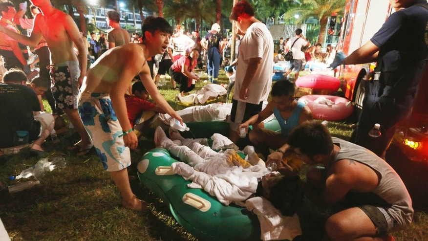 June 27, 2015: Emergency rescue workers and concert spectators tend to injured victims from an explosion during a music concert at the Formosa Water Park in New Taipei City, Taiwan.