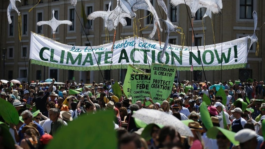 "People hold a banner reading ' Climate action Now ' in St. Peter's Square, at the Vatican, Sunday, June 28, 2015. Greeting people Sunday from his studio window, Francis praised a few hundred people who marched to St. Peter's Square under the banner ""one Earth, one family."" Marchers included Christians, Muslims, Jews, Hindus and others. Their route began near the French embassy to remind people of a climate change conference in Paris later this year. (AP Photo/Andrew Medichini)"