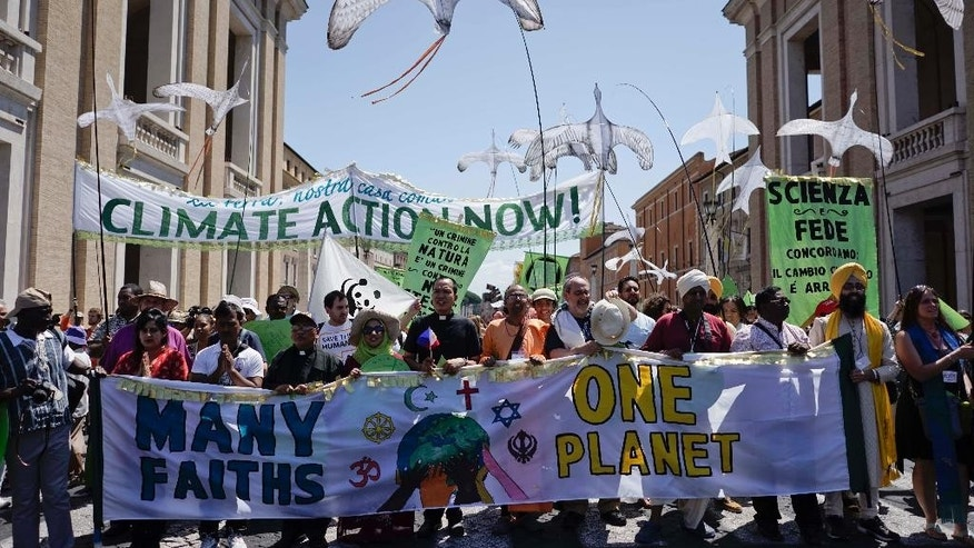 "People hold banners reading ' Climate action Now ' and ' Many Faiths, One Planet ' in St. Peter's Square, at the Vatican, Sunday, June 28, 2015. Greeting people Sunday from his studio window, Francis praised a few hundred people who marched to St. Peter's Square under the banner ""one Earth, one family."" Marchers included Christians, Muslims, Jews, Hindus and others. Their route began near the French embassy to remind people of a climate change conference in Paris later this year. (AP Photo/Andrew Medichini)"