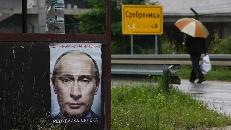 "A Bosnian man passes by a poster of Russian President Vladimir Putin plastered on bus station at the entrance to the town of  Srebrenica 150 kms north east of Sarajevo , on Sunday, June, 28, 2015. Less than two weeks before the Srebrenica massacre's 20th anniversary, Muslims and Eastern Orthodox Serbs in the Bosnian town are as divided as ever. Serbs have put up anti-European Union posters and posters of Russian President Vladimir Putin with the words ""Republika Srpska,"" or ""Serb Republic,"" on a warehouse where Serb forces executed Muslim Bosnians during the 1995 genocide. The Serbs say the posters are meant as an anti-EU protest and to call for Russia to veto a British-drafted U.N. resolution that honors the Srebrenica victims and suggests July 11 should be a memorial day. (AP Photo/Amel Emric)"