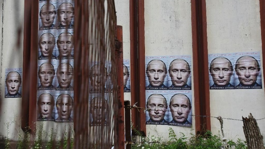"Posters displaying Russian President Vladimir Putin are plastered on a bullet-riddled walls of a warehouse in the village of Kravica, near Srebrenica,150 kms north east of Sarajevo, Sunday, June, 28, 2015. Less than two weeks before the Srebrenica massacre's 20th anniversary, Muslims and Eastern Orthodox Serbs in the Bosnian town are as divided as ever. Serbs have put up anti-European Union posters and posters of Russian President Vladimir Putin with the words ""Republika Srpska,"" or ""Serb Republic,"" on a warehouse where Serb forces executed Muslim Bosnians during the 1995 genocide. The Serbs say the posters are meant as an anti-EU protest and to call for Russia to veto a British-drafted U.N. resolution that honors the Srebrenica victims and suggests July 11 should be a memorial day. (AP Photo/Amel Emric)"