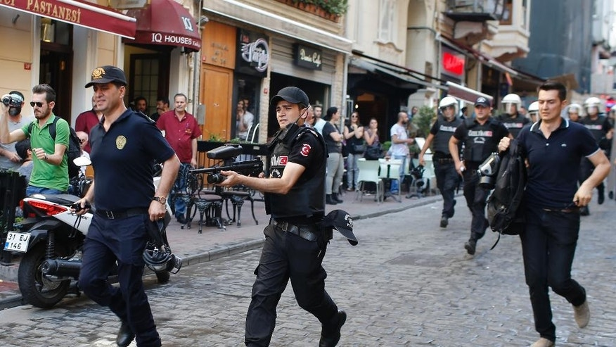 Turkish police, one holding a rubber bullet rifle, center, run to disperse participants of a Gay Pride event in support of  Lesbian, Gay, Bisexual and Transsexual (LGBT) rights in Istanbul, Sunday, June 28, 2015. Turkish police have used water cannons and tear gas to clear gay pride demonstrators from Istanbul's central square. It wasn't immediately clear why the police intervened to push the peaceful if noisy protest away from the area. Demonstrators regrouped a few blocks down the street and continued to dance and chant slogans against homophobia without any further clashes. (AP Photo/Emrah Gurel)