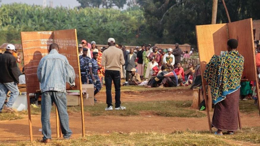 Burundian people complete their ballot papers while others wait to vote in parliamentary elections in Ngozi, Burundi, Monday, June 29, 2015.  Burundians are voting in parliamentary elections marked by an opposition boycott and the threat of violence as police battle anti-government protesters in the capital. (AP Photo/Gildas Ngingo)