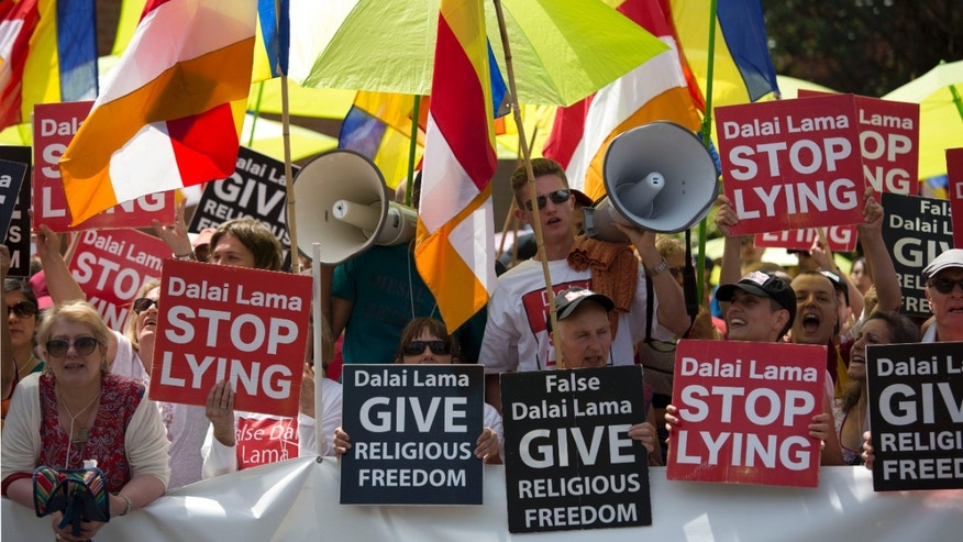 Monday, June 29, 2015: Buddhists and supporters of the International Shugden Community protest against the Dalai Lama across the street from the ESS Stadium as he makes a speech to an audience inside the stadium in Aldershot, southern England.