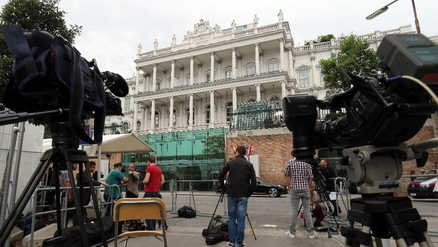 Journalists and journalists are waiting in front of Palais Coburg where closed-door nuclear talks with Iran take place in Vienna, Austria, Monday, June 29, 2015. (AP Photo/Ronald Zak)